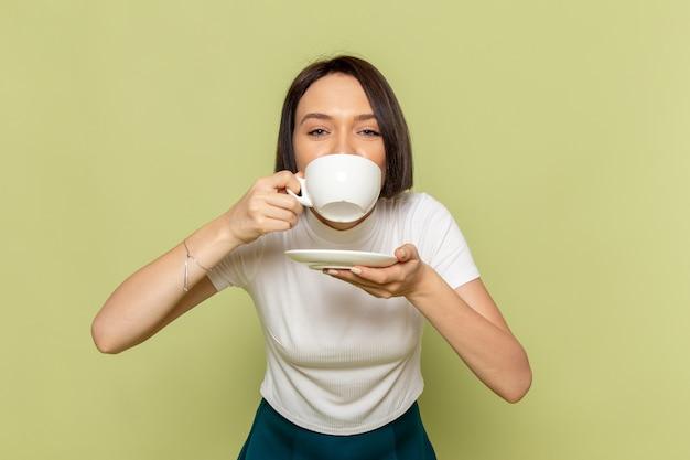 Mulher de blusa branca e saia verde bebendo chá