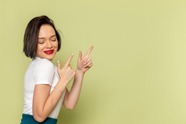 Mulher de blusa branca e saia verde posando com um sorriso