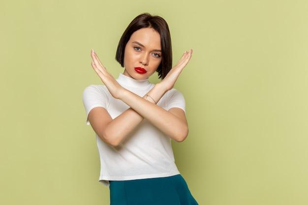 Mulher de blusa branca e saia verde posign e mostrando sinal de proibição