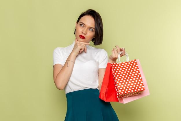 Mulher de blusa branca e saia verde segurando pacotes de compras com expressão pensativa