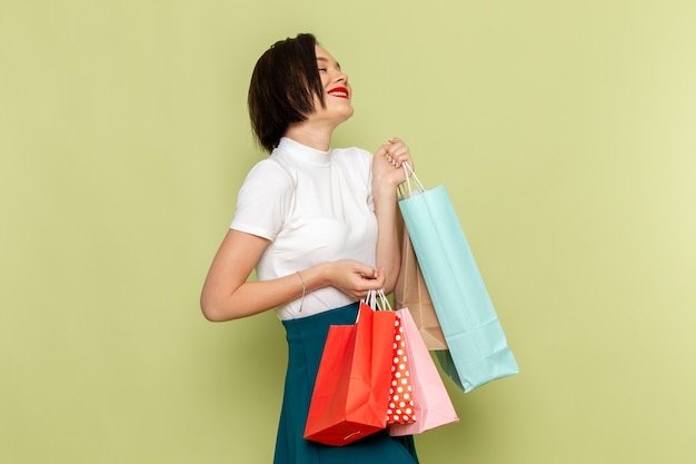 Mulher de blusa branca e saia verde segurando pacotes de compras com sorriso e pose de modelo de roupas femininas