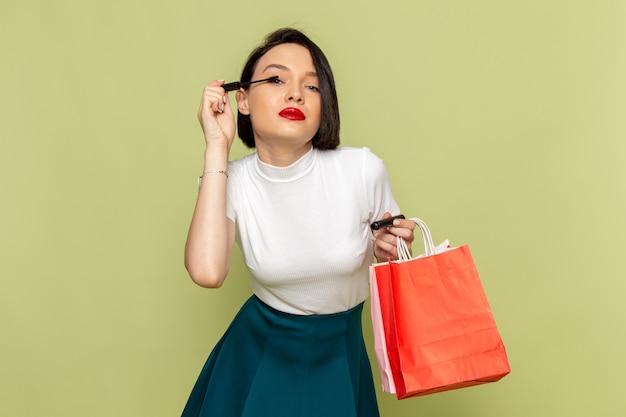 Mulher de blusa branca e saia verde segurando pacotes de compras e fazendo maquiagem