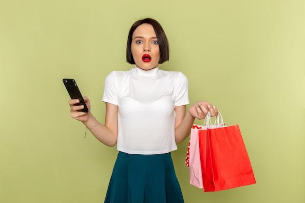 Mulher de blusa branca e saia verde segurando pacotes de compras