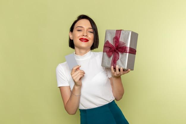 Mulher de blusa branca e saia verde segurando um cartão cinza e uma caixa de presente