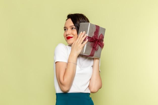Mulher de blusa branca e saia verde segurando uma caixa de presente
