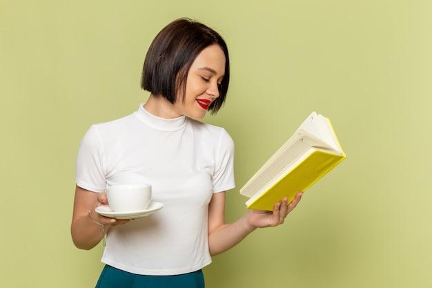 Mulher de blusa branca e saia verde segurando uma xícara de chá e lendo um livro