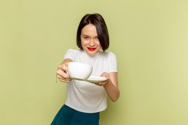 Mulher de blusa branca e saia verde segurando uma xícara de chá