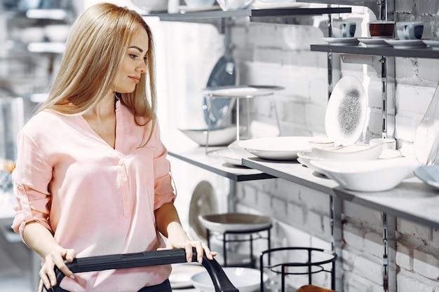 Mulher de blusa rosa compra pratos na loja