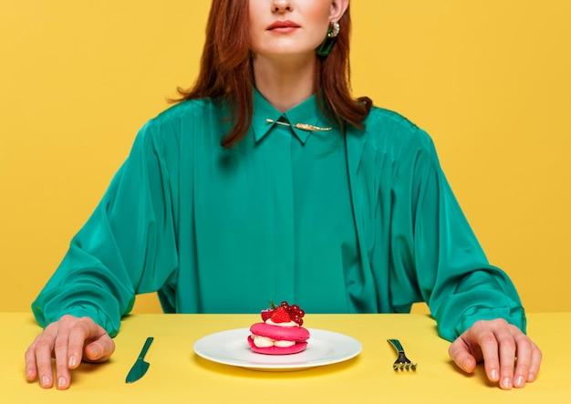 Mulher de blusa verde sentada ao lado de um bolo delicioso