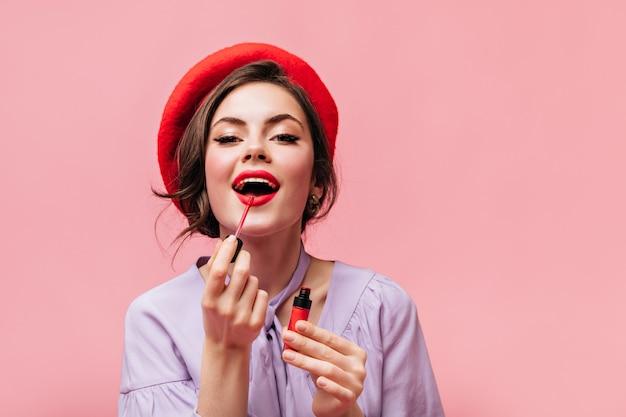 Mulher de boina brilhante pinta os lábios com batom vermelho. menina na blusa lilás, posando em fundo rosa.