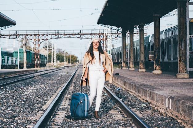 Mulher de boina e jaqueta bege, esperando o trem na estação de trem.