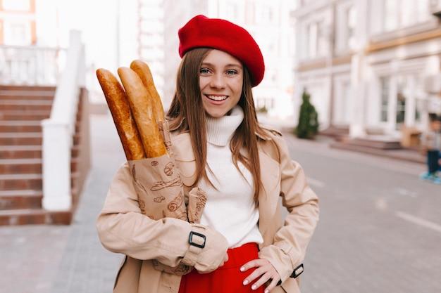 Mulher de boina vermelha com saco de baguetes andando em casa com um sorriso feliz