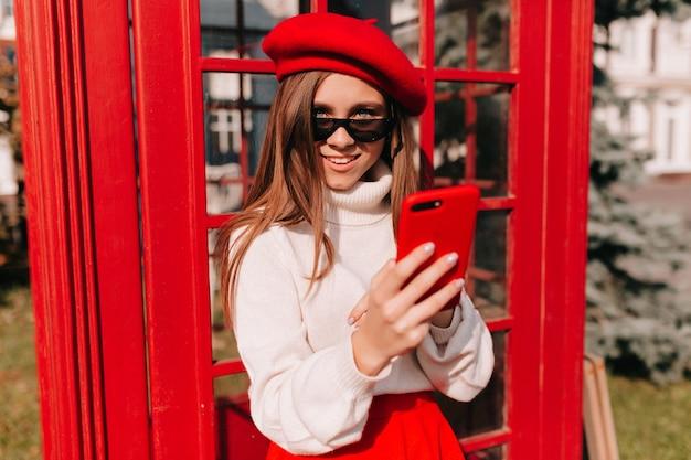 Mulher de boina vermelha com smartphone na rua