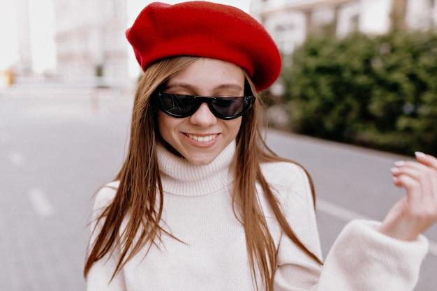 Mulher de boina vermelha posando na rua