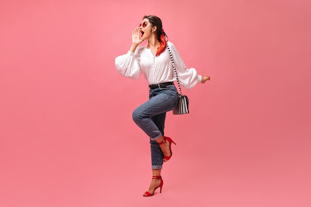 Mulher de bom humor grita no fundo rosa. menina elegante em blusa branca, jeans e salto alto, posando com bolsa listrada.