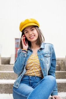 Mulher de boné e jaqueta jeans falando ao telefone