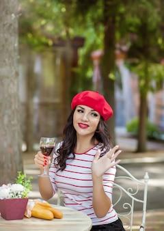 Mulher de boné vermelho bebendo vinho tinto no café ao ar livre e acenar com a mão para alguém