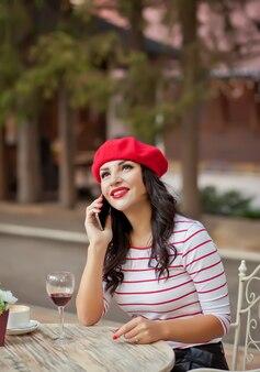 Mulher de boné vermelho bebendo vinho tinto no café ao ar livre e falando ao telefone
