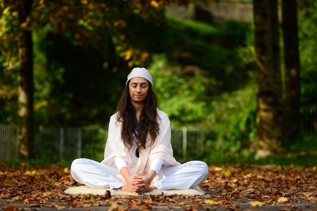 Mulher de branco no parque outono enquanto faz ioga