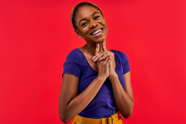 Mulher de brincos com um sorriso largo em uma camiseta azul posando para a câmera