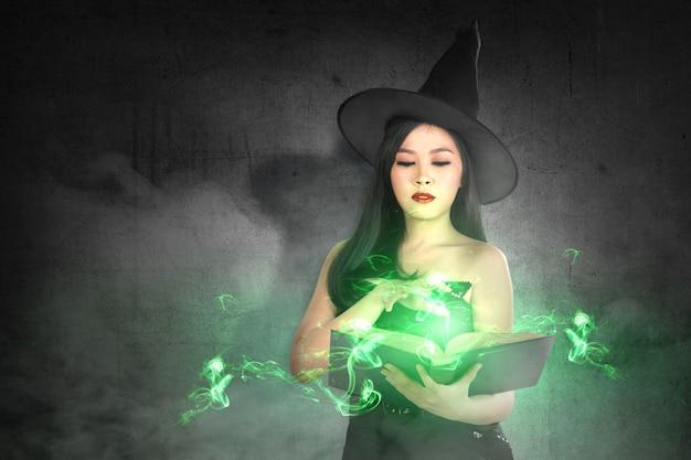 Mulher de bruxa asiática no chapéu aprende o feitiço do livro mágico