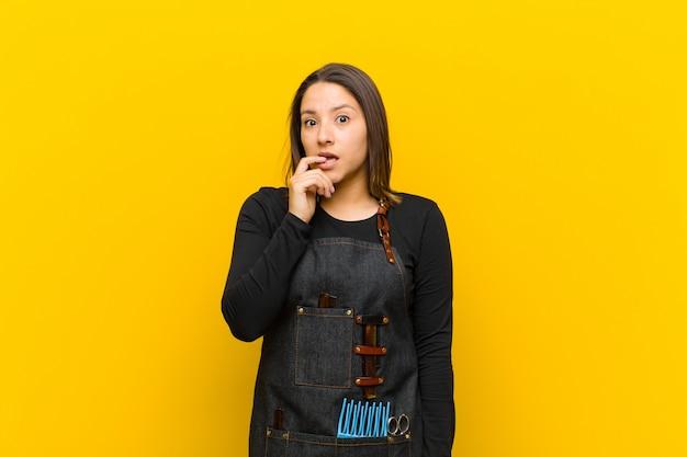 Mulher de cabeleireiro com olhar surpreso, nervoso, preocupado ou assustado, olhando para o lado em direção ao espaço da cópia contra laranja