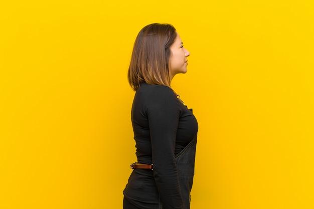 Mulher de cabeleireiro na vista de perfil, olhando para copyspace em frente, pensando, imaginando ou sonhando acordado contra laranja