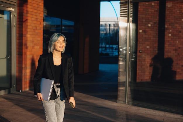 Mulher de cabelo azul andando lá fora com um computador e sorrindo alegremente
