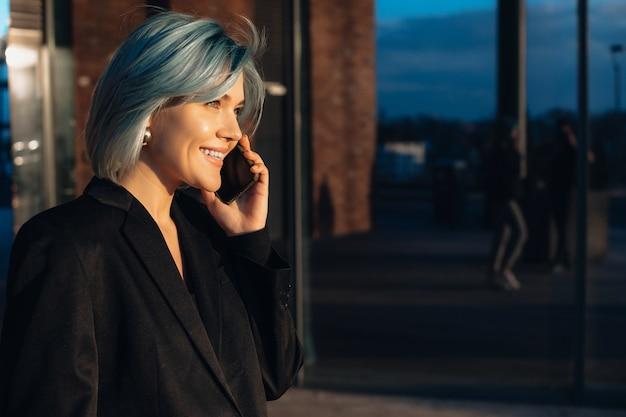 Mulher de cabelo azul falando ao telefone enquanto posa do lado de fora na frente do sol