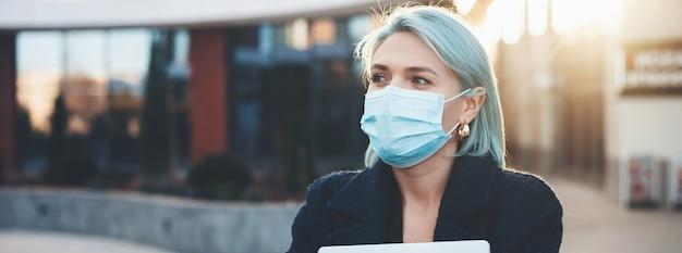 Mulher de cabelo azul posando do lado de fora com um computador enquanto usa uma máscara especial