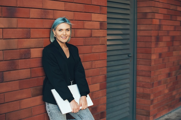 Mulher de cabelo azul posando do lado de fora em uma parede de pedra com um computador e olhando para a câmera