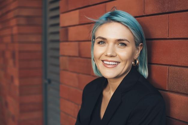 Mulher de cabelo azul posando em uma parede de tijolos sorrindo na frente em um terno de negócio