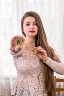 Mulher de cabelo bem comprido mostrando dois bitcoins dourados