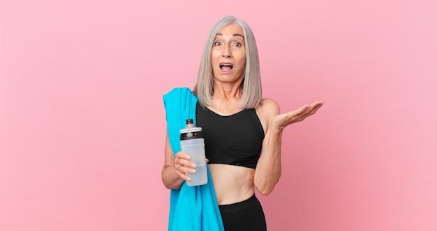 Mulher de cabelo branco de meia-idade maravilhada, chocada e atônita com uma surpresa inacreditável com uma toalha e uma garrafa de água. conceito de fitness