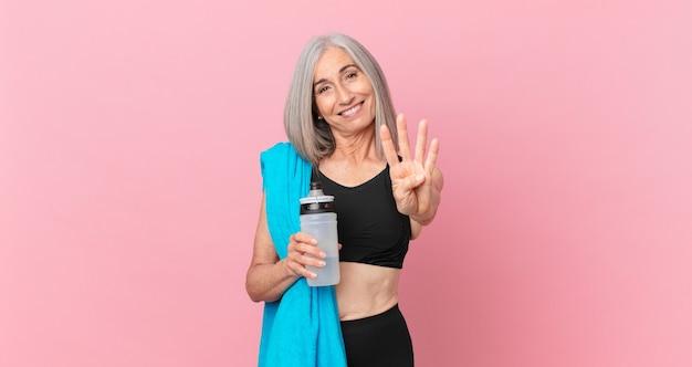 Mulher de cabelo branco de meia-idade sorrindo e parecendo amigável, mostrando o número quatro com uma toalha e uma garrafa de água