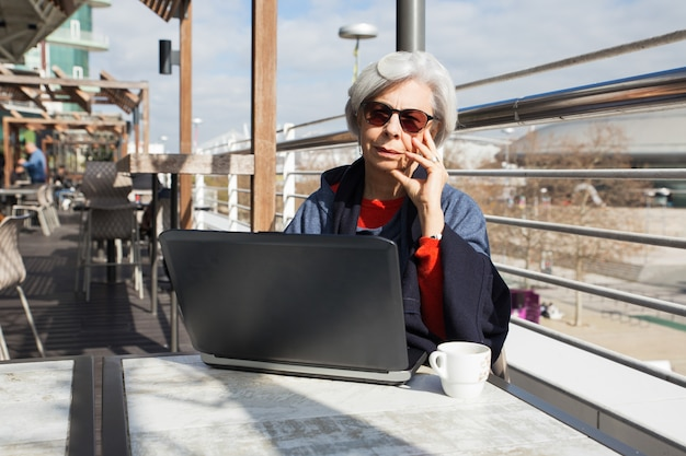 Mulher de cabelo cinza pensativa em óculos de sol usando laptop