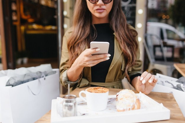 Mulher de cabelo comprido com manicure branca tirando foto do almoço em um café ao ar livre