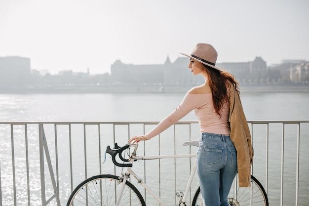 Mulher de cabelo comprido pensativa e de chapéu em pé perto de uma bicicleta, apreciando a vista do rio em um dia ensolarado