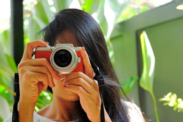 Mulher de cabelo comprido preto tirando fotos pela câmera mirrorless