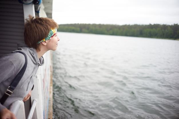 Mulher de cabelo curto caucasiano, observando a água do convés durante a viagem de navio