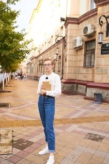 Mulher de cabelo curto com um livro nas mãos ao ar livre, lendo o estilo de vida. foto de alta qualidade