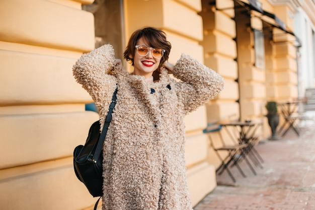 Mulher de cabelo curto e casaco sorrindo para a frente