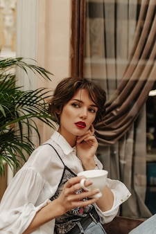 Mulher de cabelo curto em camisa de manga comprida com lábios vermelhos, segurando uma xícara de café no restaurante. mulher com poses de penteado morena no café.
