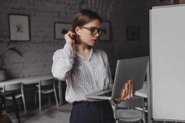 Mulher de cabelo curto em fones de ouvido fala por videochamada e segura o laptop enquanto trabalha em um escritório espaçoso.