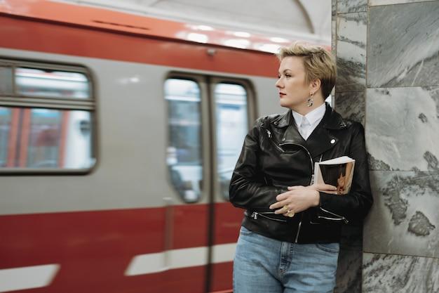 Mulher de cabelo curto em uma jaqueta de couro com um livro esperando o trem na plataforma da estação de metrô