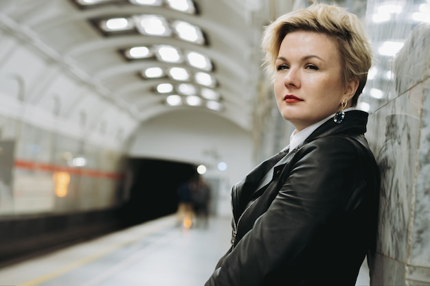 Mulher de cabelo curto em uma jaqueta de couro esperando o trem na plataforma da estação de metrô
