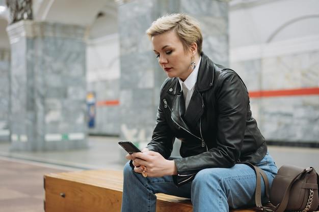 Mulher de cabelo curto em uma jaqueta de couro lendo algo no smartphone na plataforma da estação de metrô
