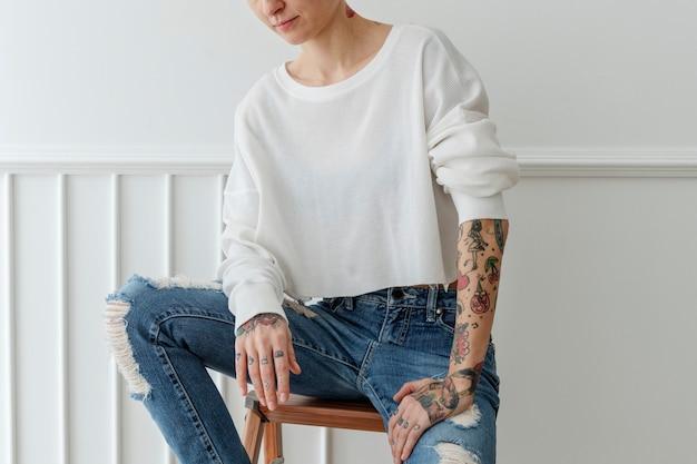Mulher de cabelo curto tatuado e descolado em jeans rasgados
