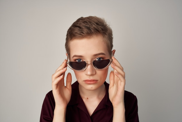 Mulher de cabelo curto usando óculos escuros glamour posando de moda