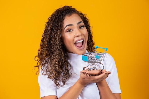 Mulher de cabelo encaracolado animado no conceito de compras. mulher jovem com um carrinho em miniatura. comércio eletrônico e negócios. carrinho de compras. mulher compradora. fundo amarelo.